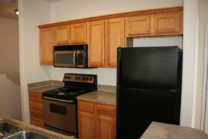 Interior of Lawrence apartment kitchen with black appliances